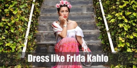 """For your own beautiful Frida Kahlo costume, you will need a Latina style skirt and top, lots of intricate and nature inspired jewelry, and an iconic rose or flower headband to top it all off""."
