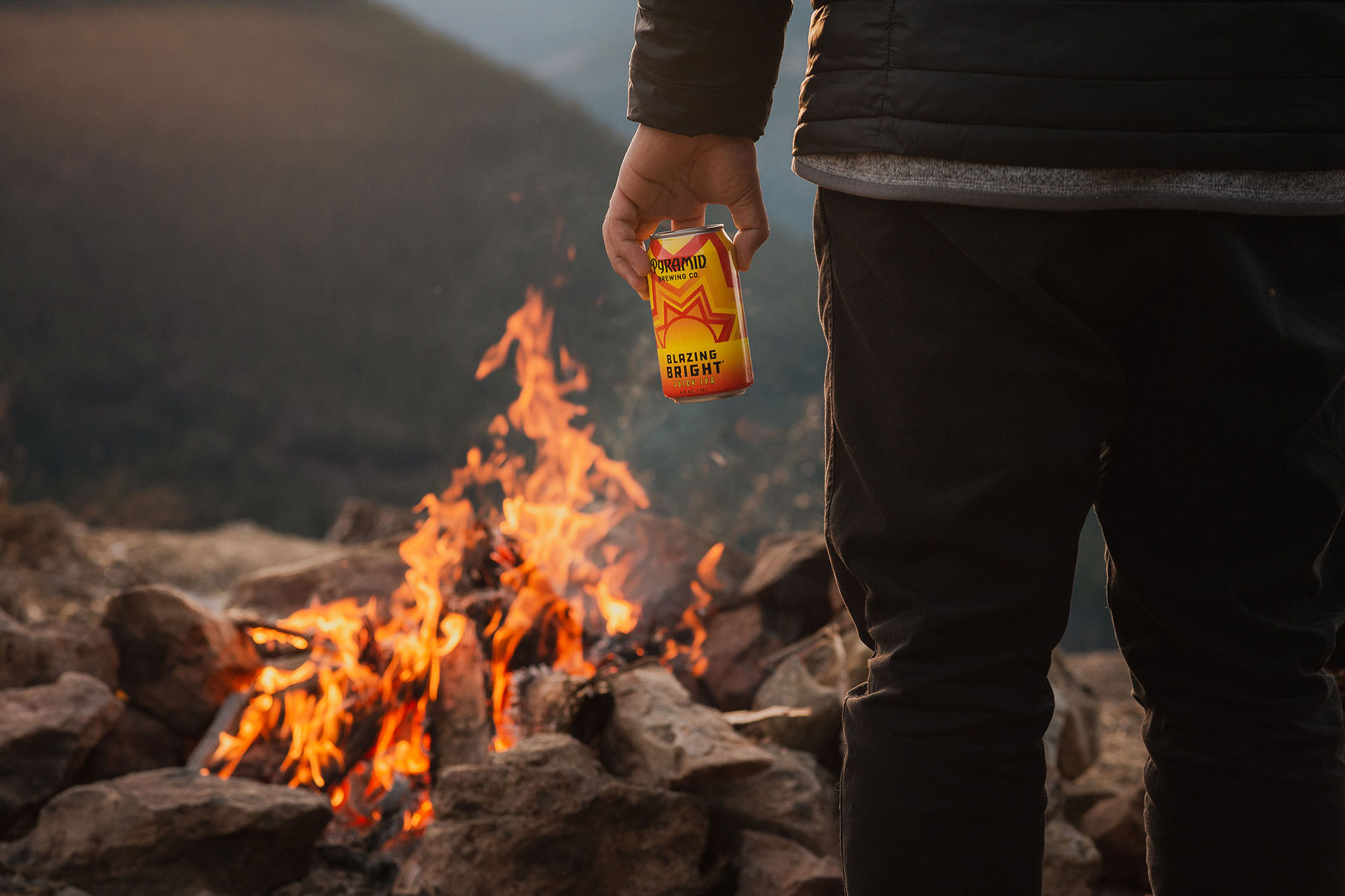 Gentlemen from behind holding a Blazing Bright can with a campfire in the background