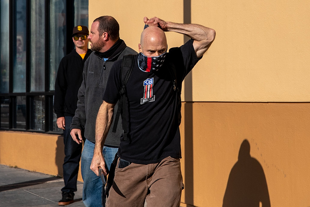 Neo-Nazi who brandished a knife straightens his gaiter and walks toward antifascist counter-protestors.