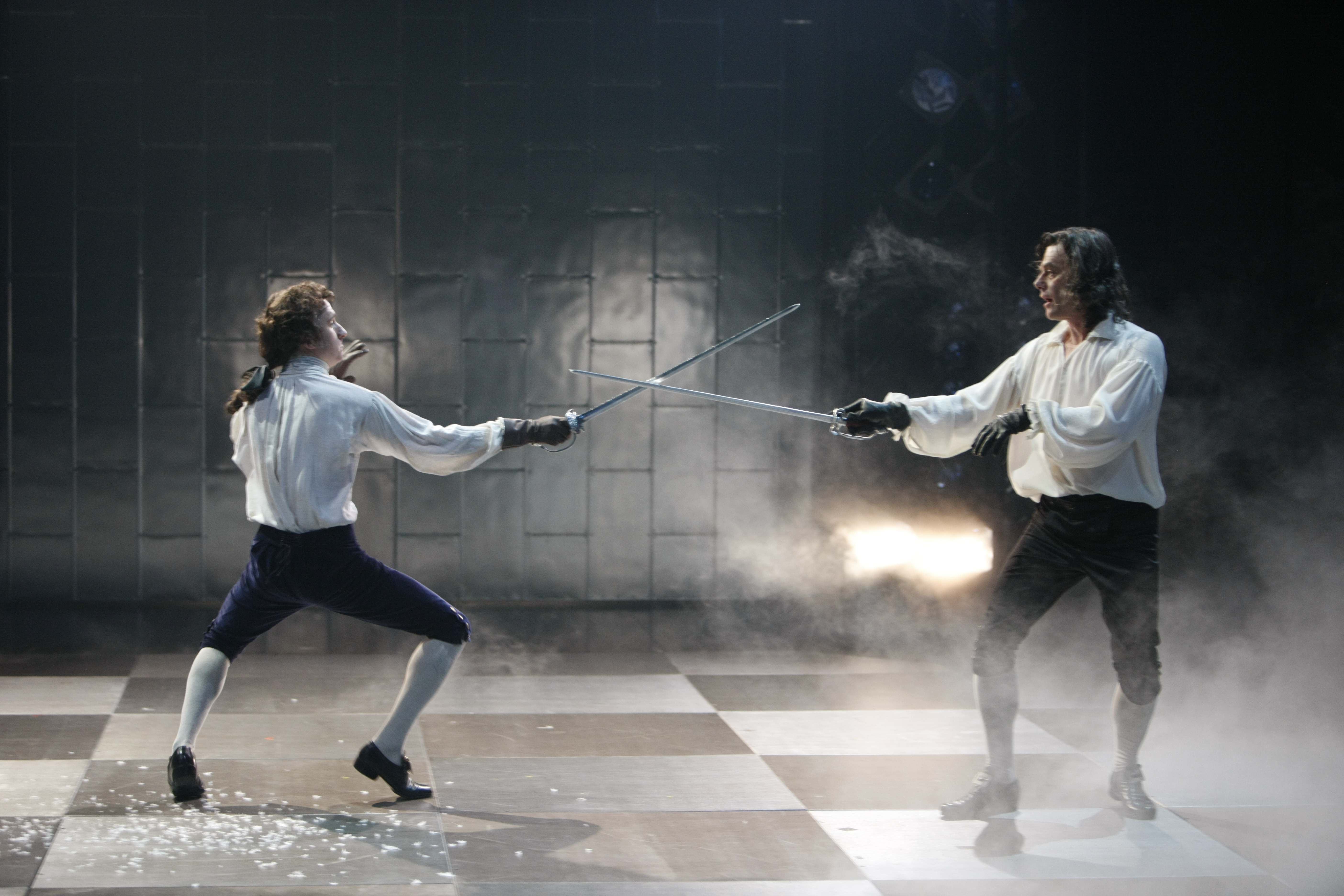 Two men in white shirt sleeves duel with swords in smoke on checkered stage.