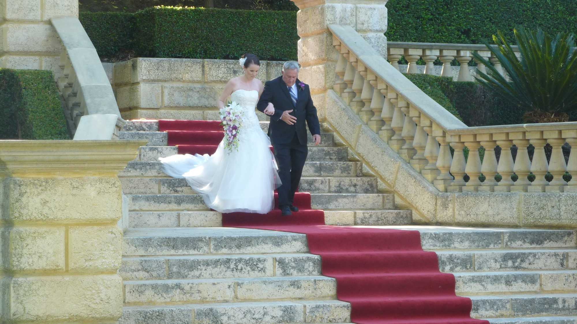 Photo of a bride being walked down a large set of sandstone steps by her father, walking down the aisle lined with a long red carpet. It's outdoors and there are hedges and greenery all around.