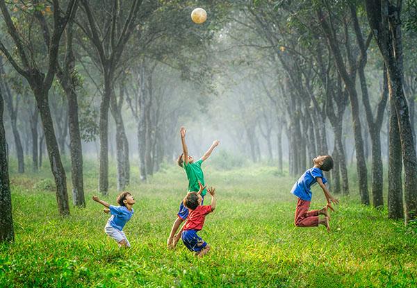 niños saltaldo con un balon en la hierba
