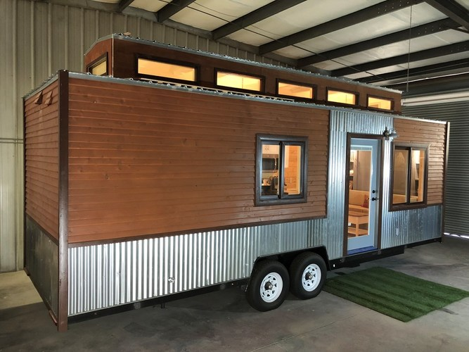 External view of this tiny home on wheels, showing 8 windows and the windowed front door.
