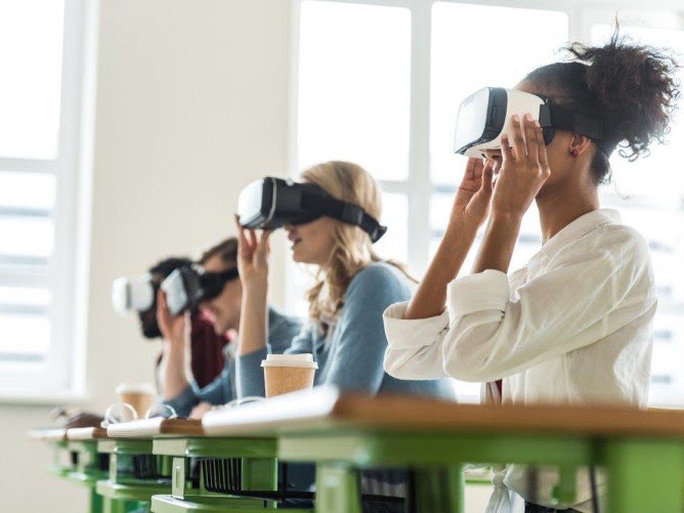 Students wearing VR headsets sit at desks in a classroom.