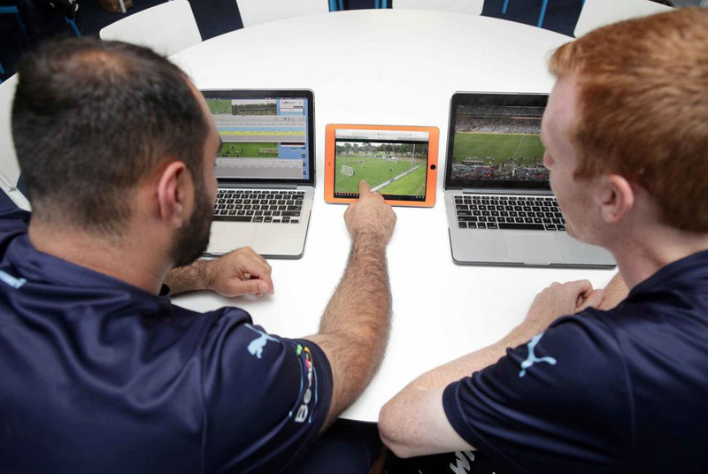 Two soccer players watching videos of gameplay on laptops and tablet