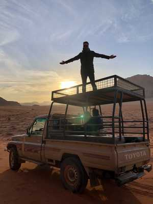 Dan Furze, on top of a Jeep, in the Wadi Rum desert, Jordan.
