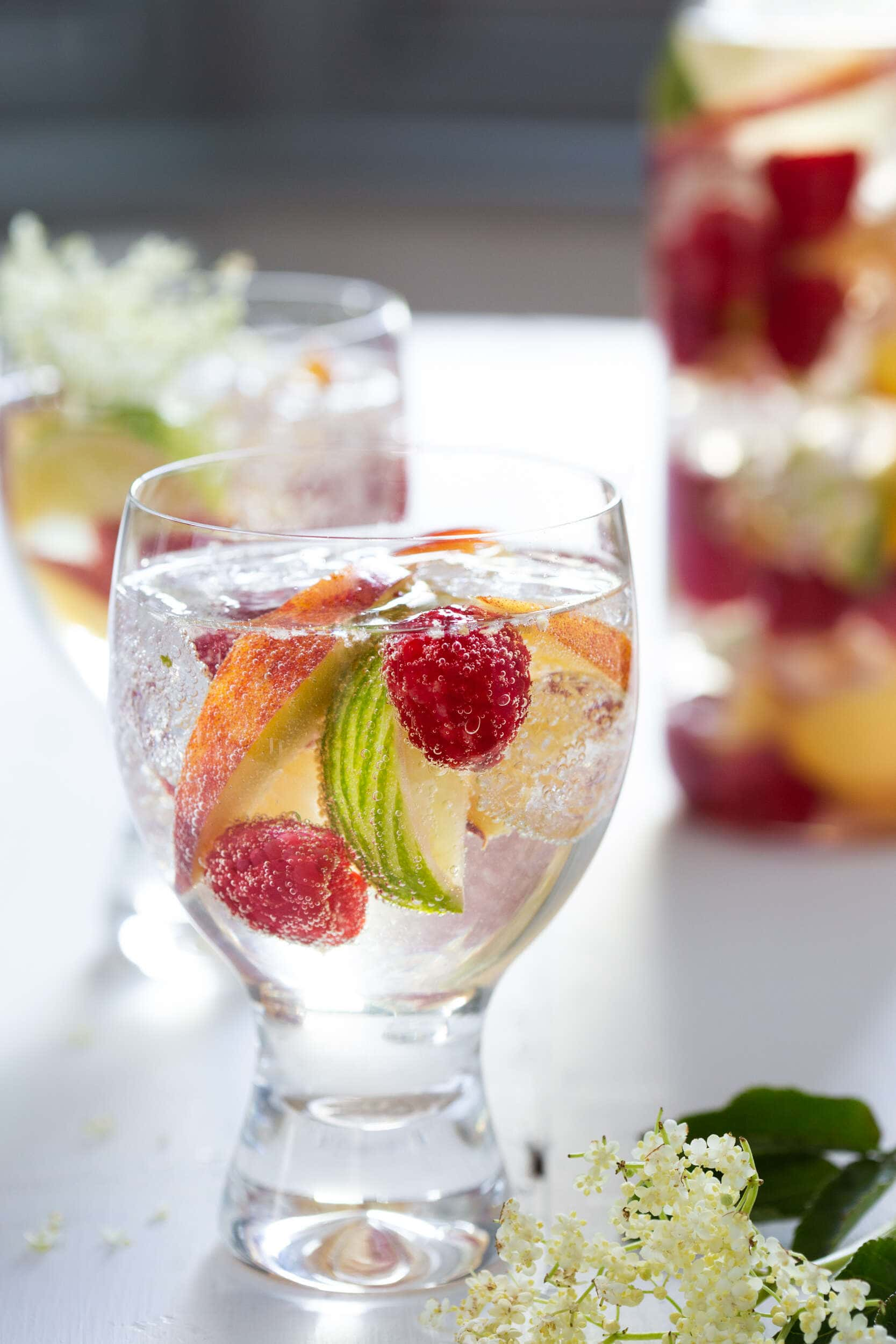 White wine sangria with elderflower, raspberries, peaches and lime in a glass with a jug of the same in the background.