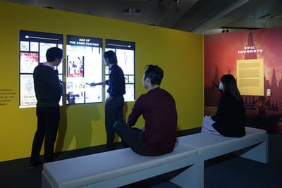 There are two people browsing 3 tall multimedia screens on the wall, with two more people sitting on the bench behind them. On their right, a wall is titled 'Epic Journeys'.