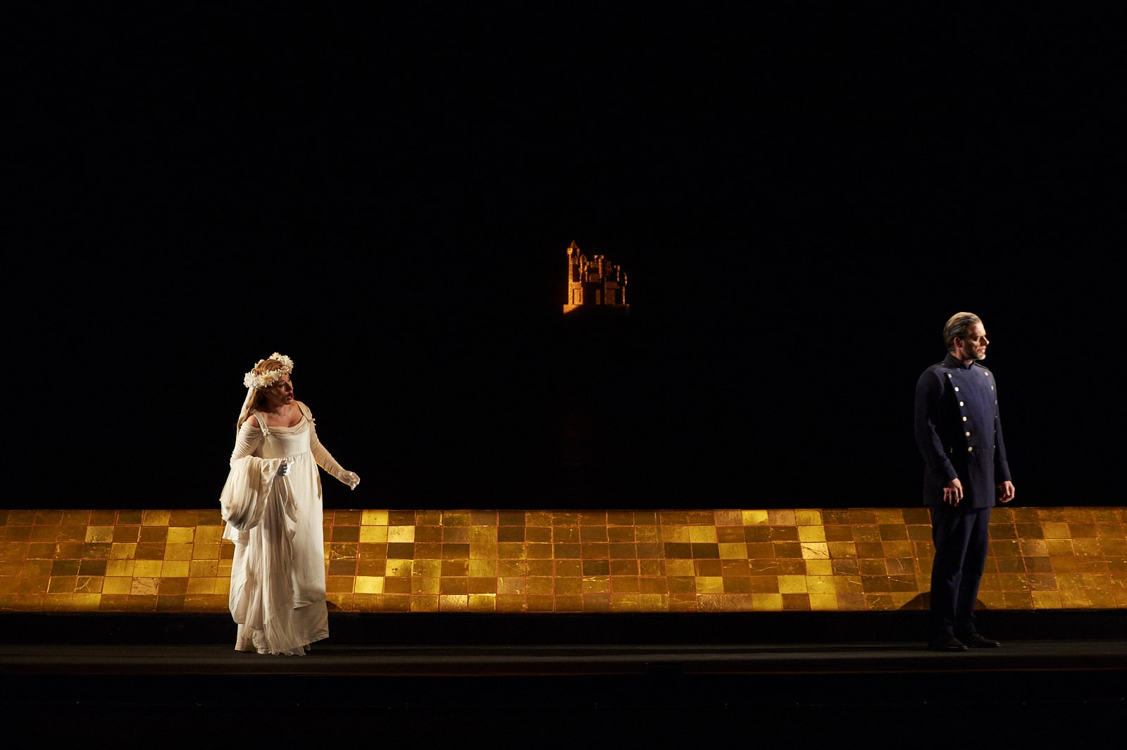 Bride with floral crown speaks to blue-uniformed man in front of gold-tiled path with miniature castle spotlight in background.