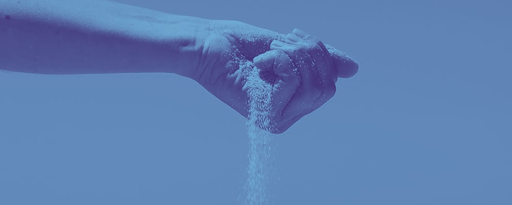 hand with sand falling between fingers