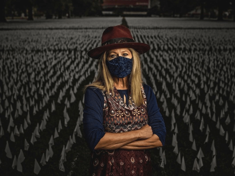 Artist Suzanne Brennan stands in front of white flags commemorating lives lost to COVID-19.