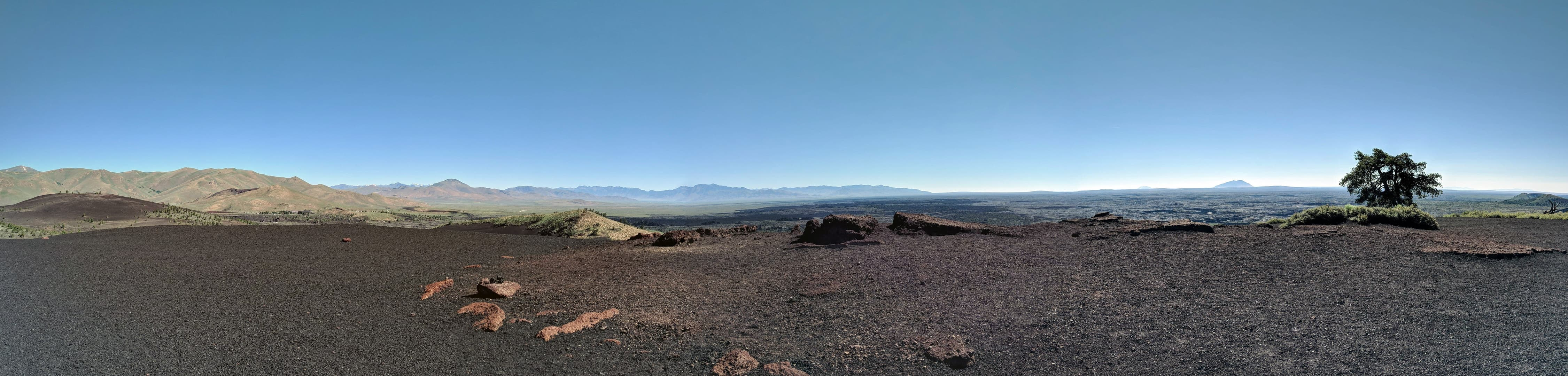 A panorama taken from the top of a black volcanic cinder cone across an immense lava field. Mountains dominate the left, but to the right the barren lava field stretches to the horizon. In the far distance, an immense lava dome rises above the horizon.
