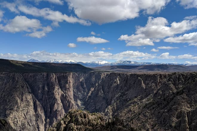 The view straight into the steep, jagged mouth of the Black Canyon of the Gunnison. In the distance, a range of domed, snow-covered peaks.