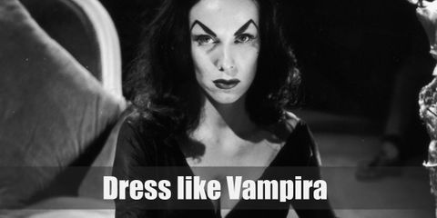 Vampira wears a skin tight black dress with a plunging neckline and billowing bat-like sleeves. She also wears a nice black waist belt.