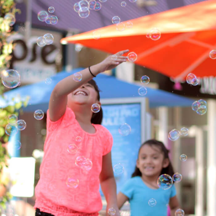 Girl smiling surrounded by bubbles.