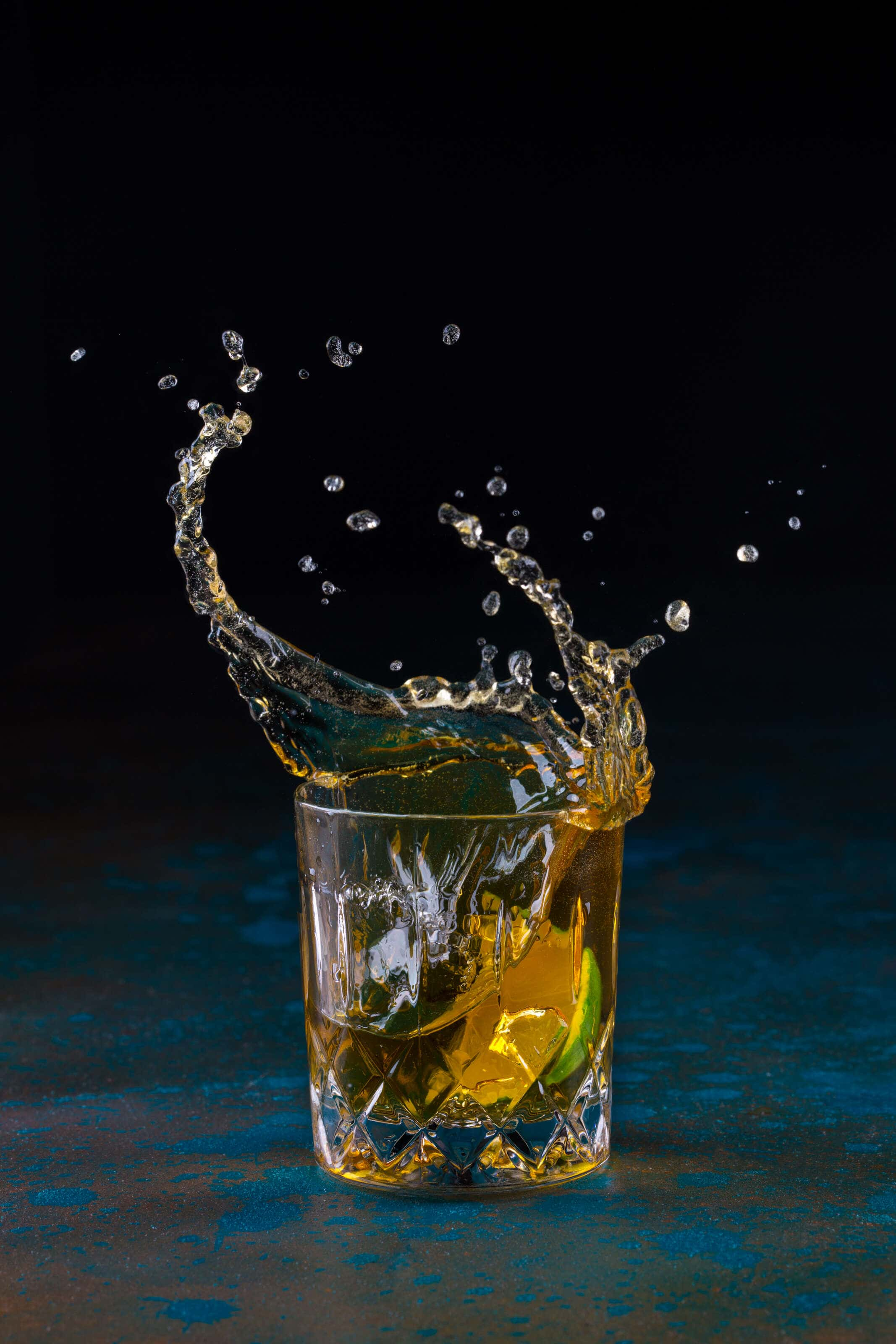 rum cocktail with a lime being dropped into it causing a splash.