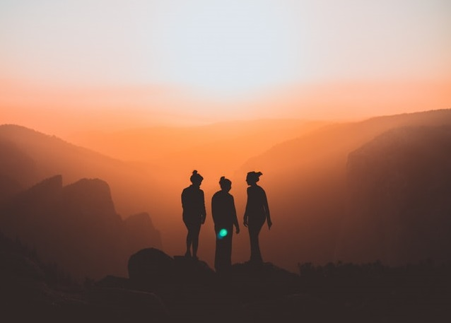 Three women stand in sillhoute atop a mountain on a hazy yellow day at sunset.