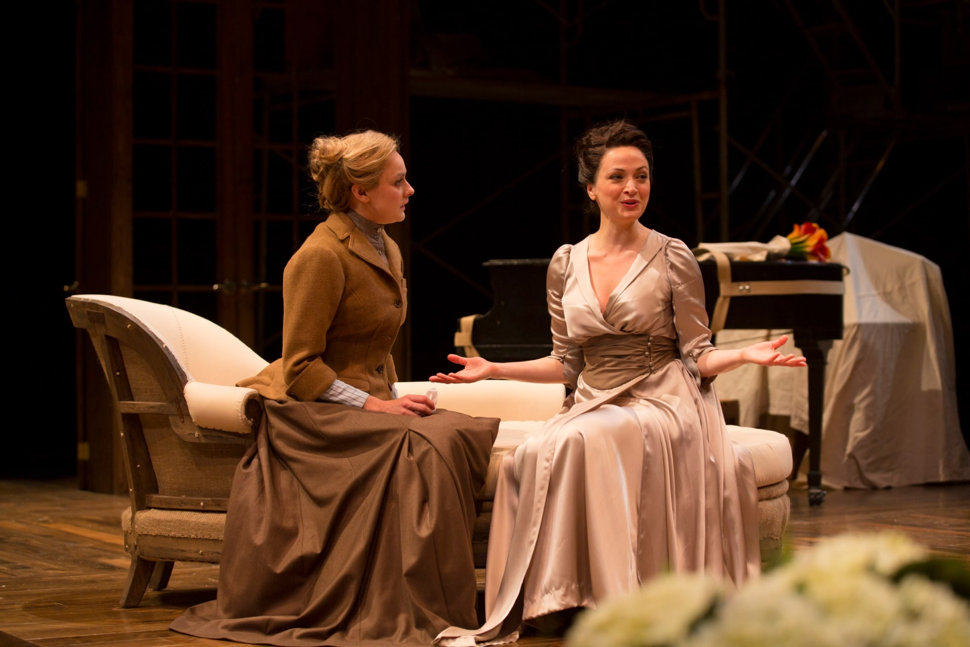 Woman in white silk gown sits speaking with woman in brown suit dress on settee.