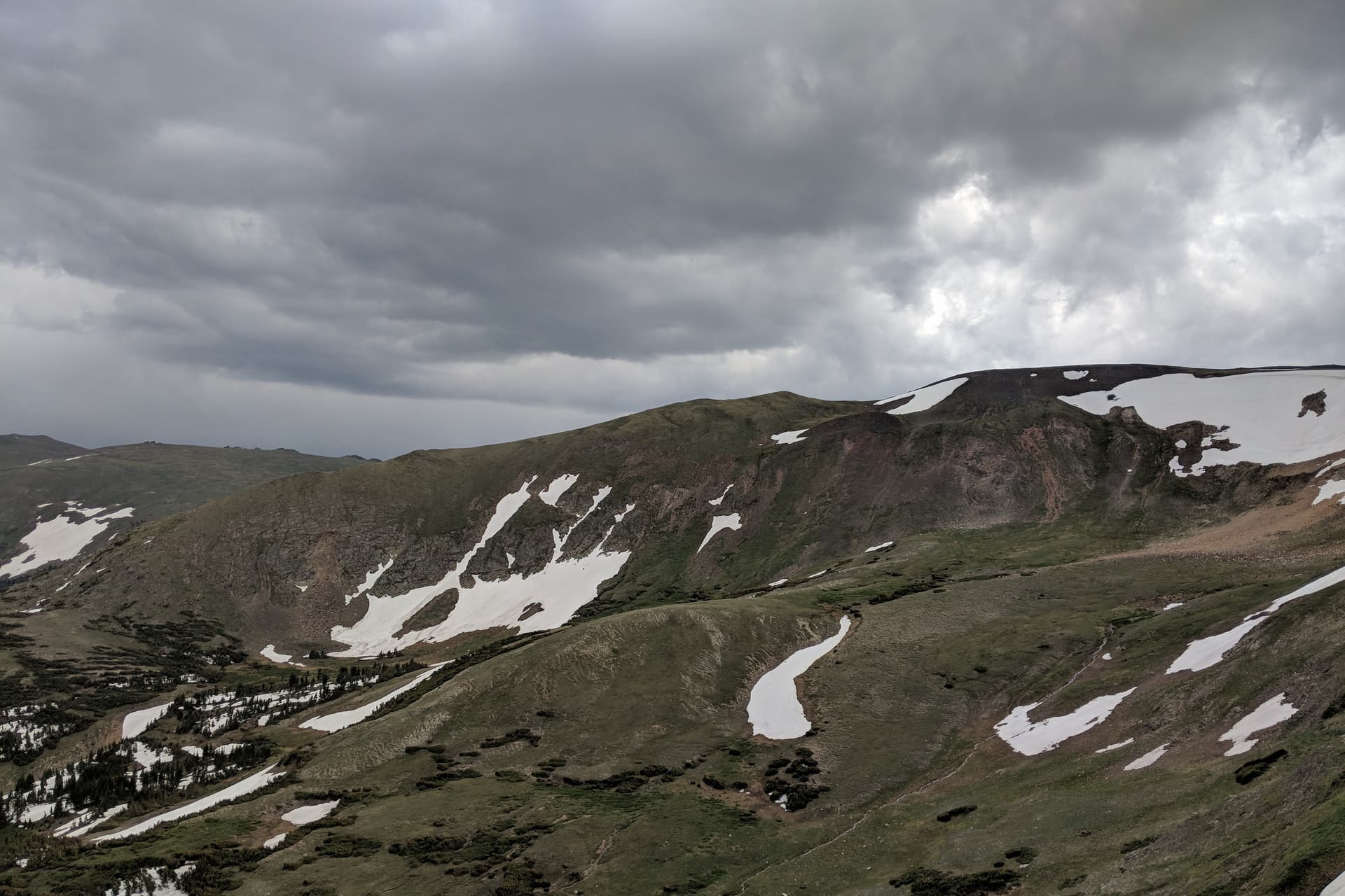 A green alpine peak, still partially covered in snow. Low, gray clouds hang overhead.