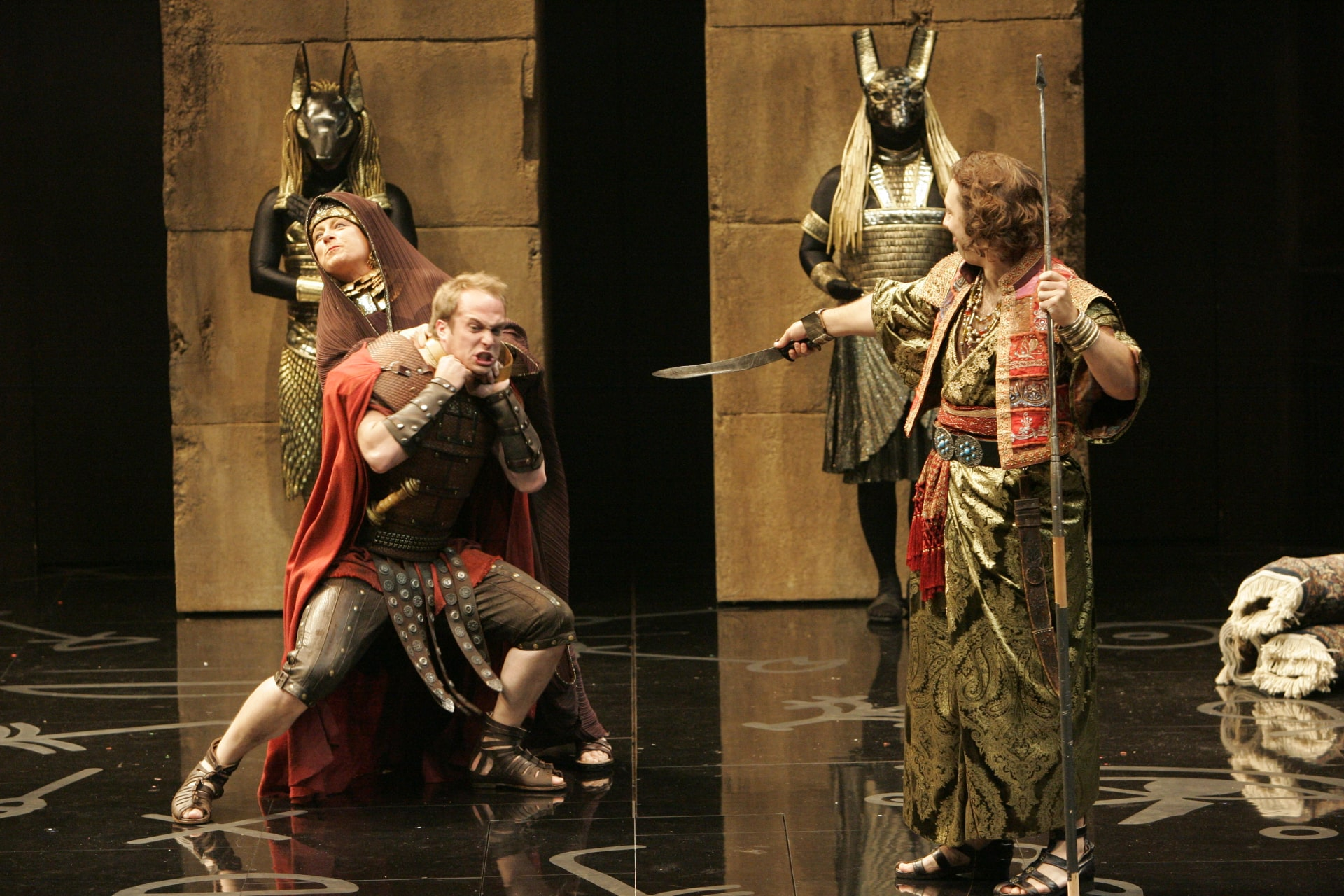 Merchant in ornate costume mocks Roman soldier being chocked by woman on shiny black floor.