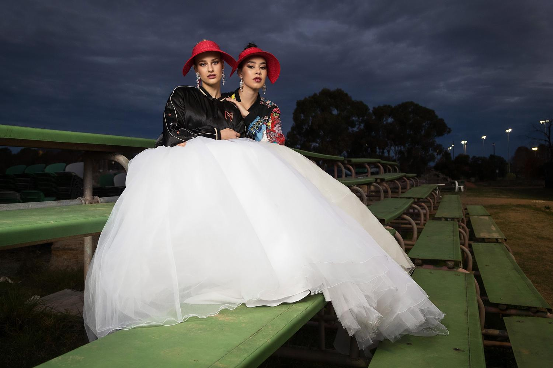 Two women on bleachers in red hats
