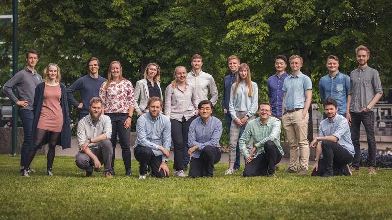 Bilde av 18 studenter som poserer til et gruppebilde i to rader på gresset. Det er fem kvinner og resten menn. Alle har lys hud.
