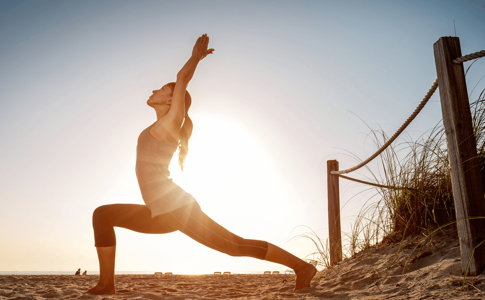 a woman doing a yoga pose on the beach