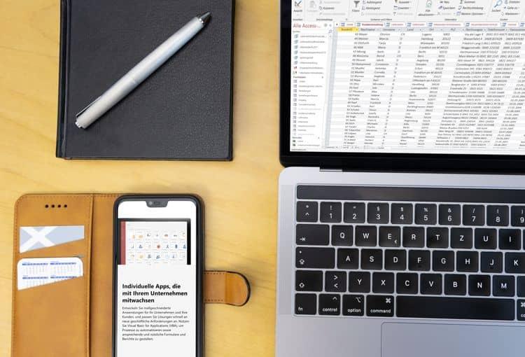 Schreibtisch mit Access auf Laptop und Smartphone und Stift