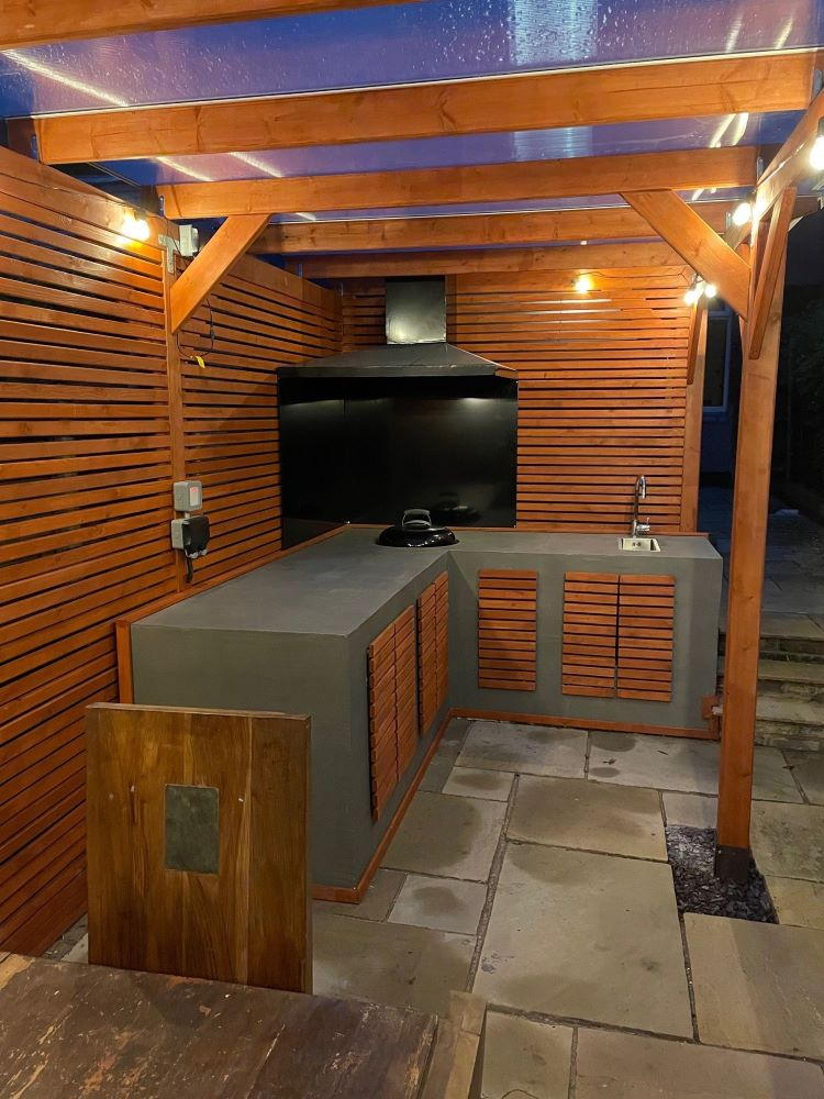 An example of a pergola with a kitchen area under it with seating at night.