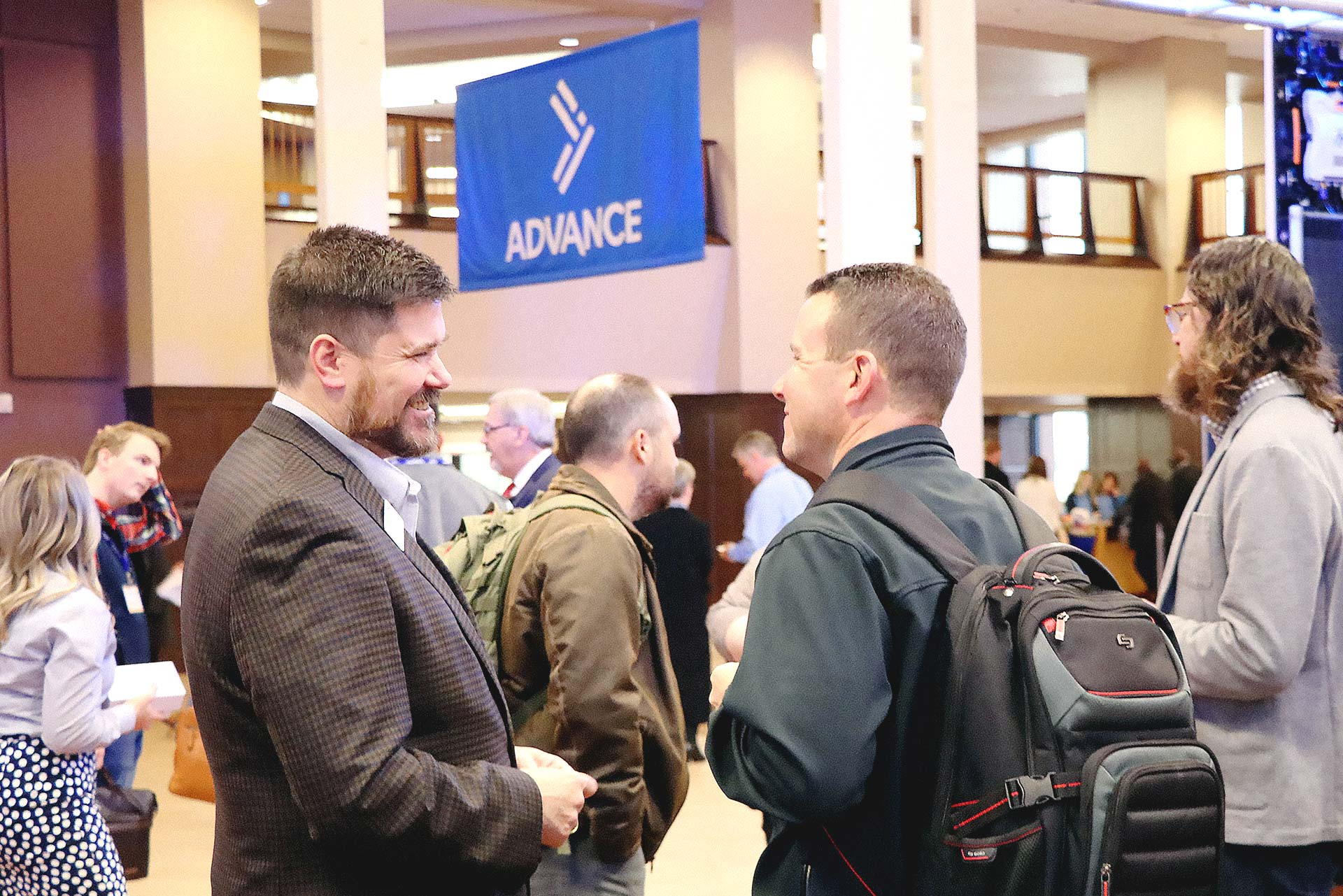 Two Oklahoma Baptists laugh, in the background is a banner using the Oklahoma Baptists logo icon.