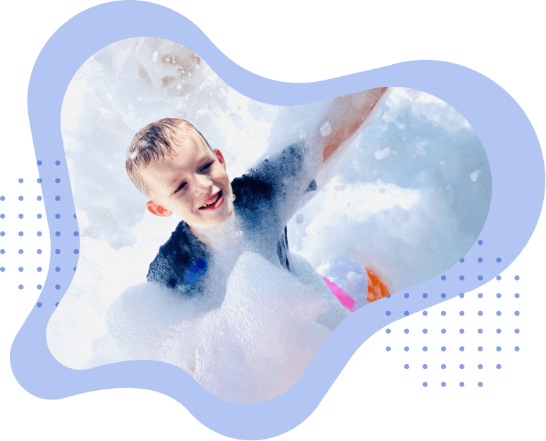Boy with blue shirt at a foam party.