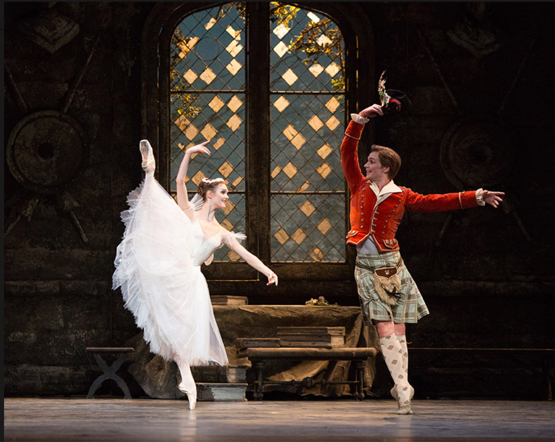 Ballerina in white dress leaps on point beside dancer in kilt and red jacket in front of paned window.