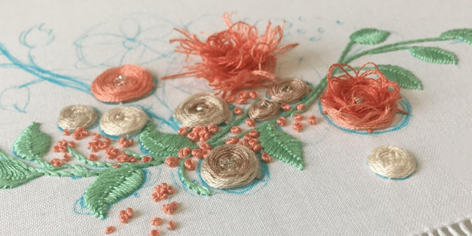 A photo of  salmon-colored flowers being embroidered onto white fabric.