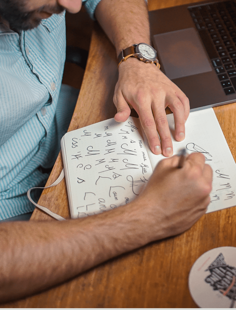 Man drawing logos in a notebook