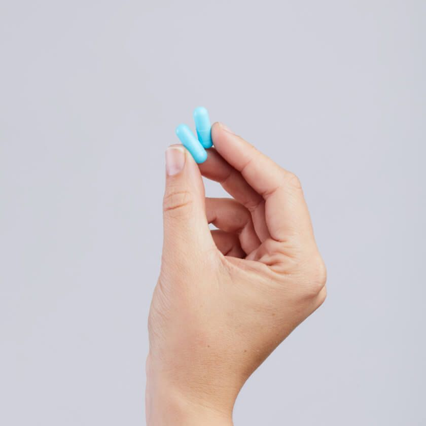 Hand holding two pills of Doxycycline.