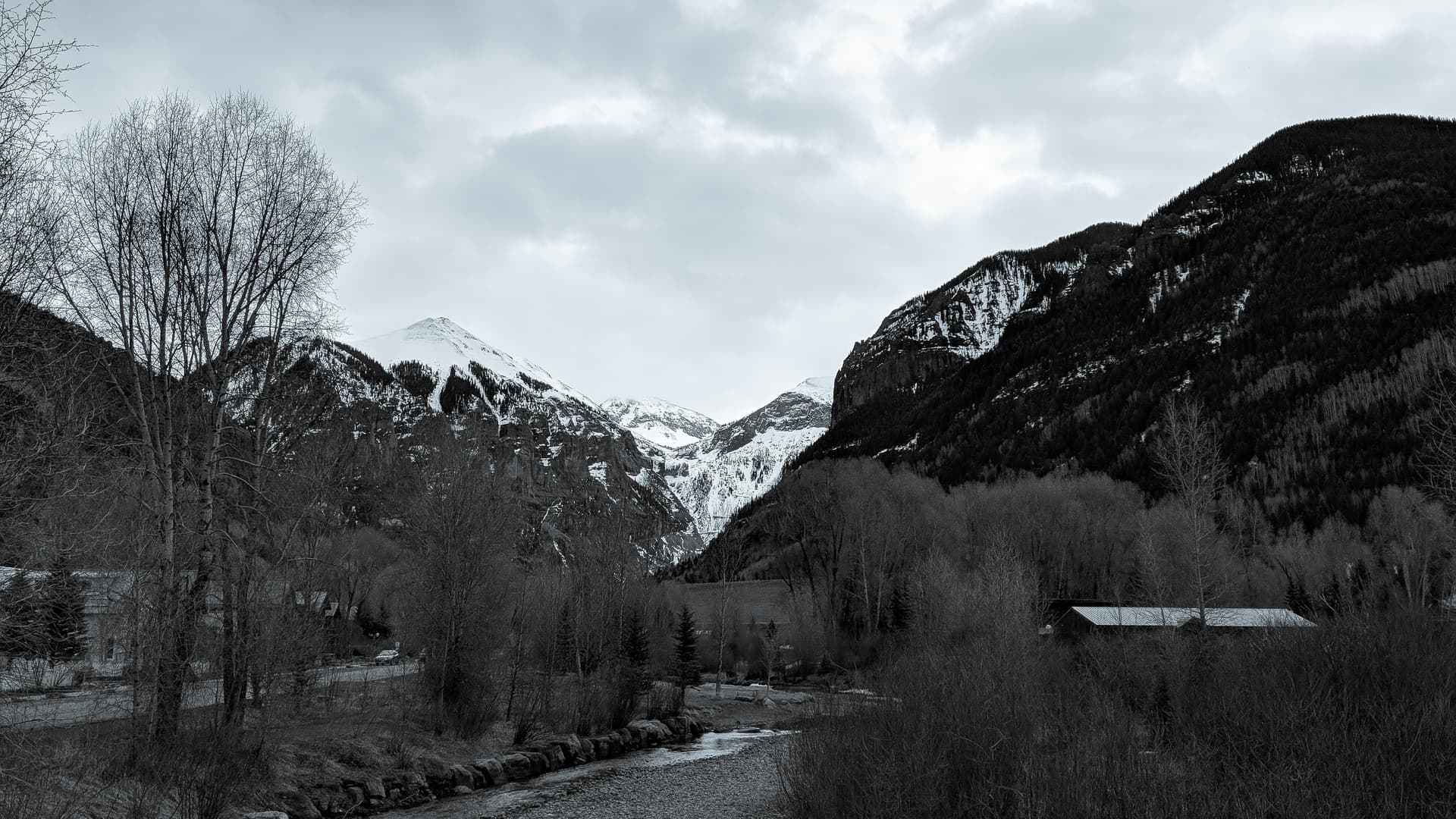 A black-and-white photo of a tree-lined mountain creek. Beyond the trees, three distinctly triangular snow-capped peaks can be seen.