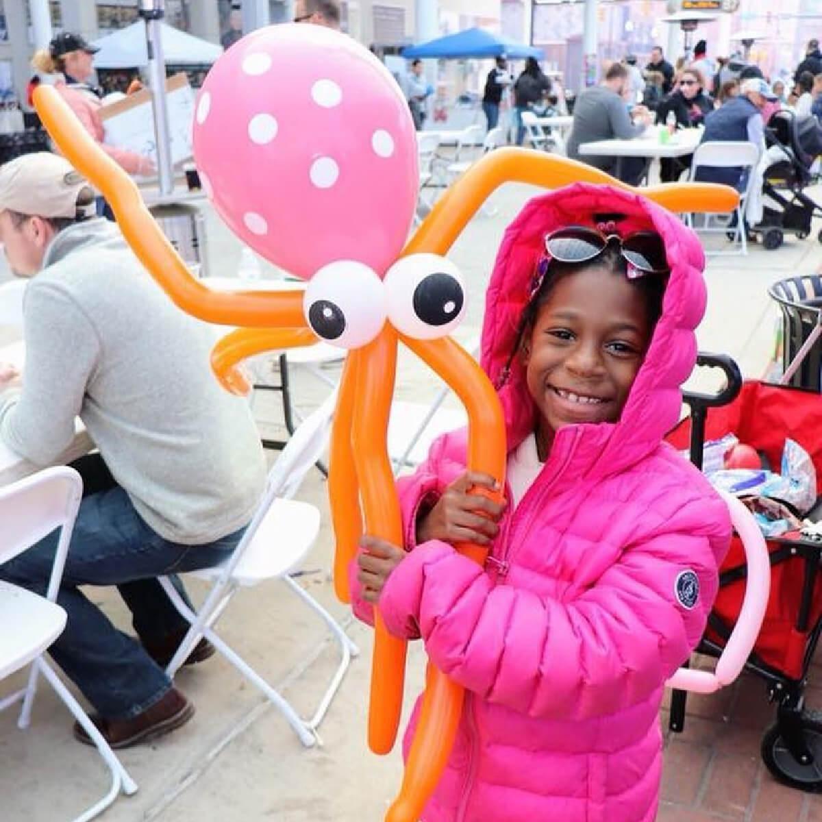 kid holding balloon animal