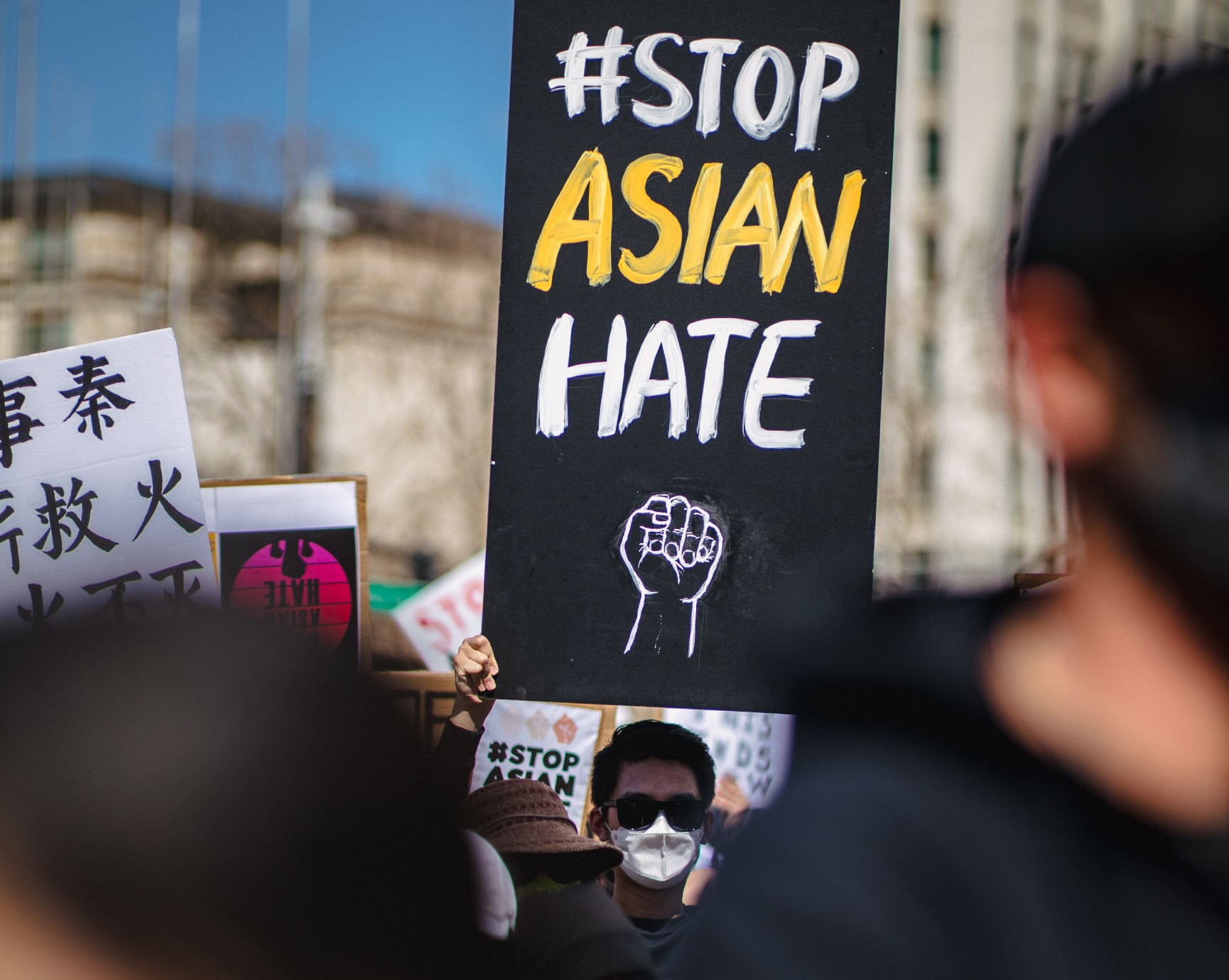 A person holds up a large #StopAsianHate sign at a large rally