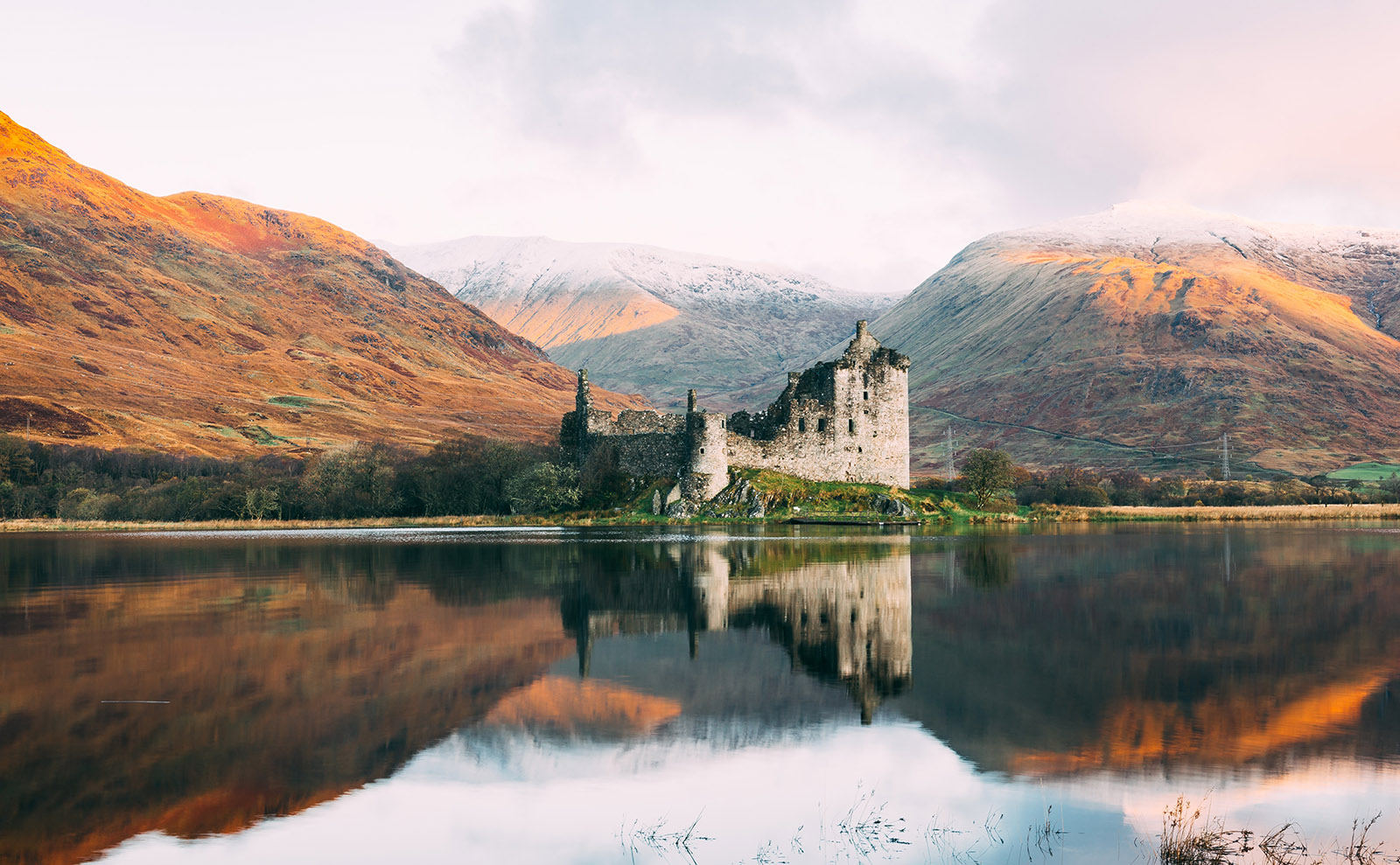 kilchurn castle in scotland surrounded by highlands
