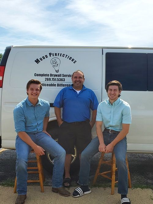 three men posing in front of the mudd perfections truck