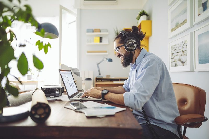 man at desk on computer working from home