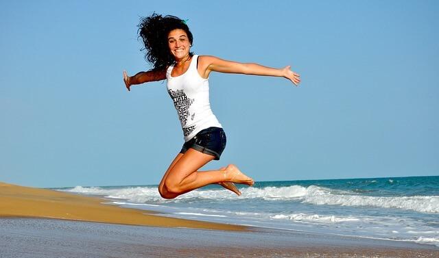 Foto de uma moça pulando na praia