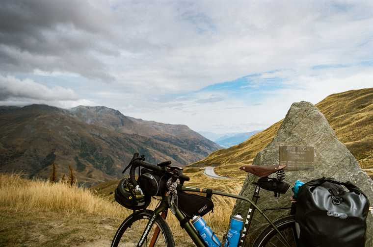 Loaded touring bike leaning against a rock overlooking a panoramic view of the New Zealand countryside with a road winding down the mountain in the distance.