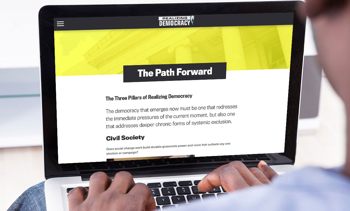 realizing democracy a path forward navigation page viewed on laptop.