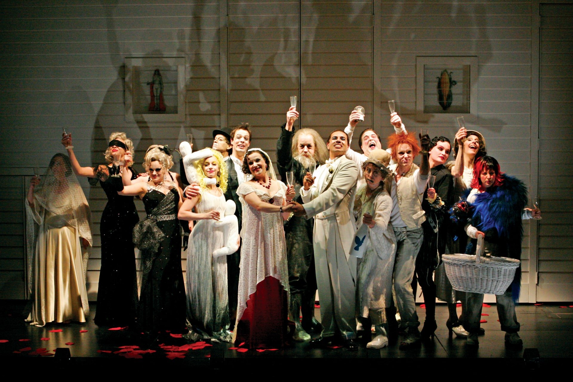Company of actors raise toast at wedding, their towering shadows on the wall behind.