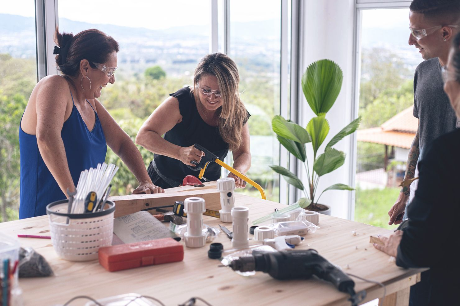 two women smile and laugh while sawing a piece of wood during a team building activity as colleagues admire their handiwork
