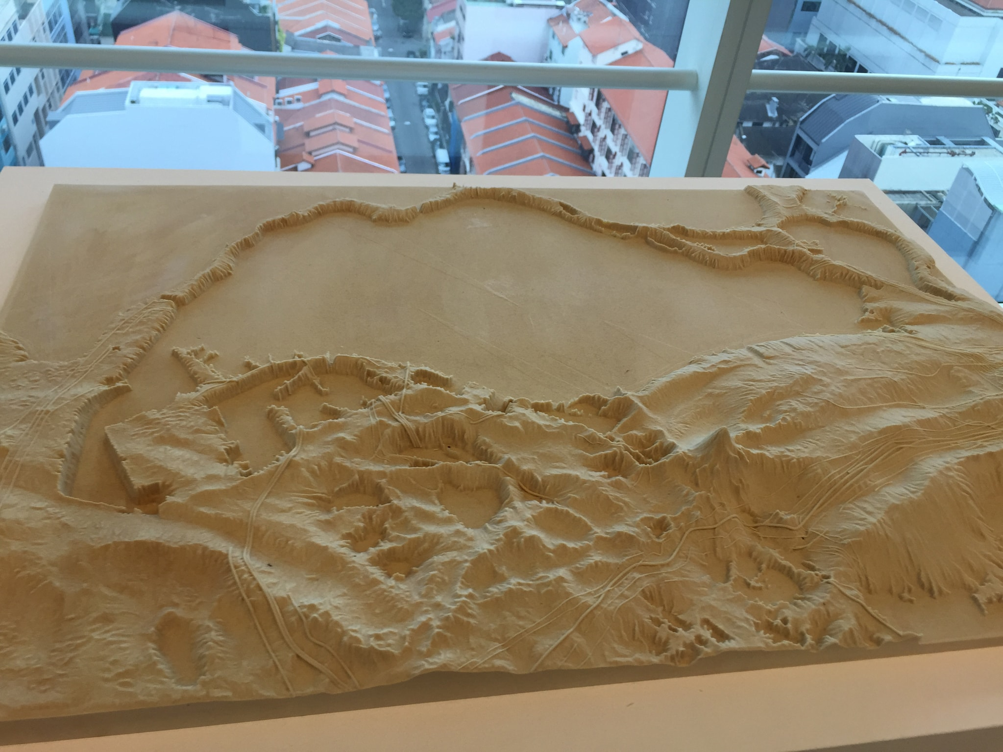 An art display, featuring a sand sculpture forming the island of Singapore.