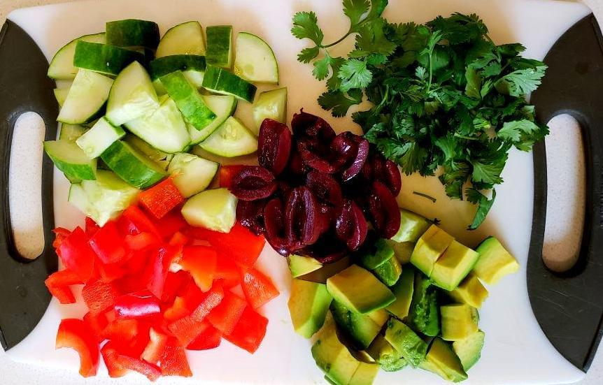 Cutting board with olives, cilantro, red pepper, cucumber, and avocado
