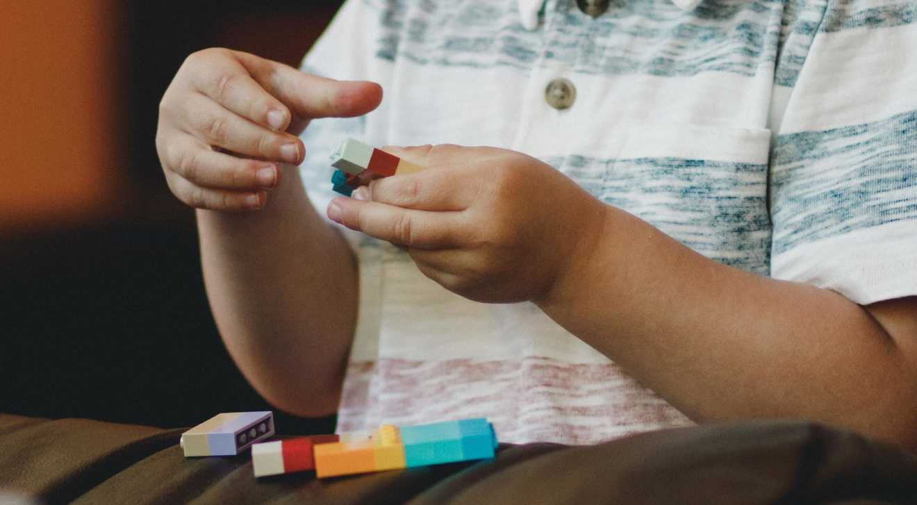 A young child with autism plays with colourful building blocks
