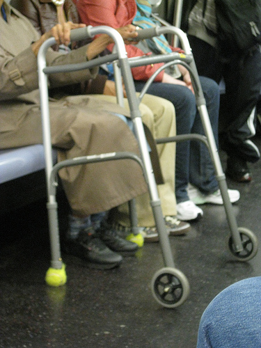 a commonly used walker mobility aid, with wheels on front and tennis balls on the back two feet